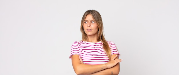 Linda mulher loira duvidando ou pensando, mordendo o lábio e sentindo-se insegura e nervosa, procurando copiar o espaço ao lado