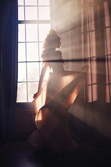 Linda mulher loira em pé na janela do sol