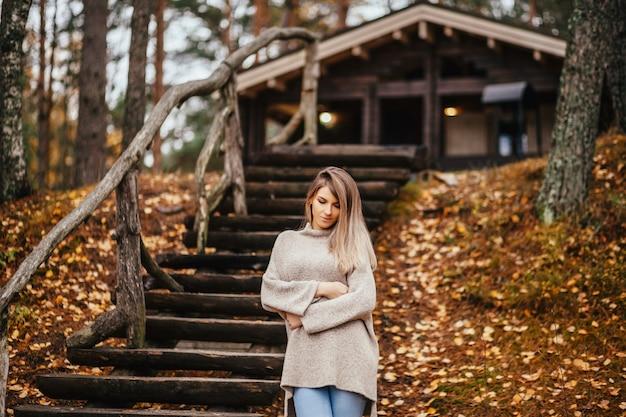 Linda mulher loira em pé perto da escada de madeira