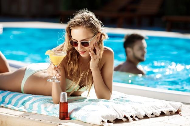 Linda mulher loira em trajes de banho tomando banho de sol, deitado perto da piscina