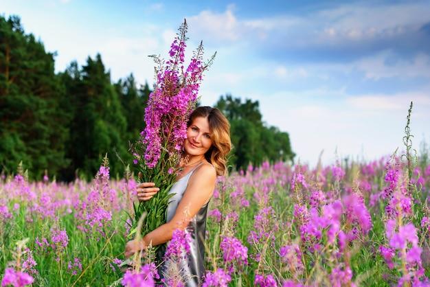 Linda mulher loira em um vestido cinza relaxando com um ramo de flores em um prado de erva.