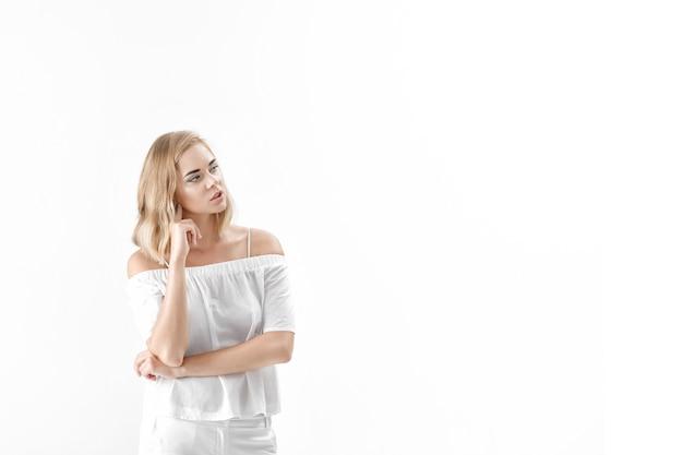 Linda mulher loira em uma blusa branca e calça em um fundo branco. cópia spase