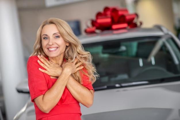 Linda mulher loira encantada com carro doado