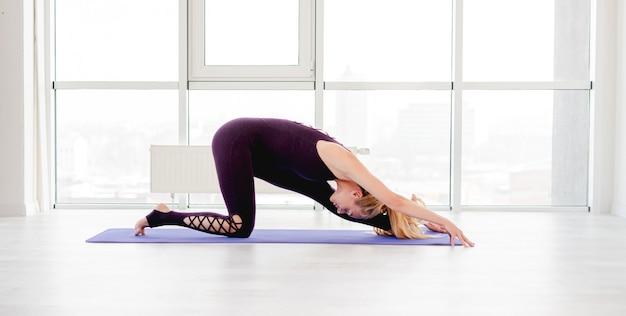 Linda mulher loira esticando a perna e as costas durante o treino de ioga matinal isolado no branco com janelas