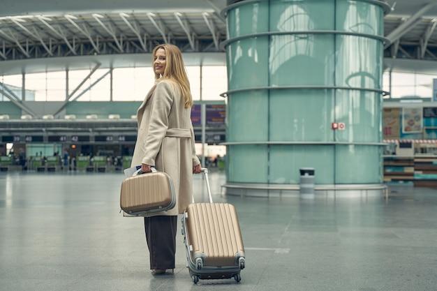 Linda mulher loira expressando positividade enquanto puxa a mala para a área do lounge