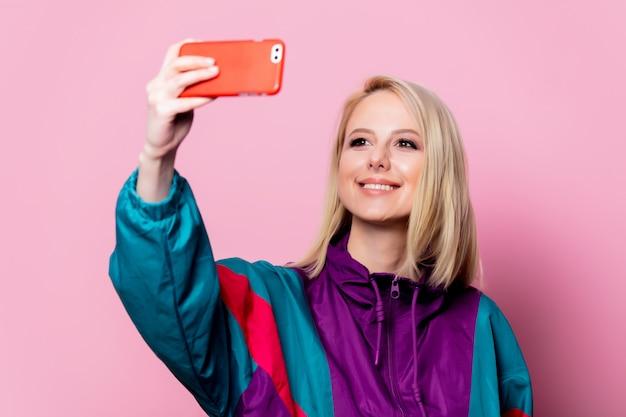 Linda mulher loira faz selfie na parede rosa
