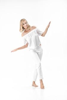 Linda mulher loira feliz em uma blusa branca e calça em um fundo branco