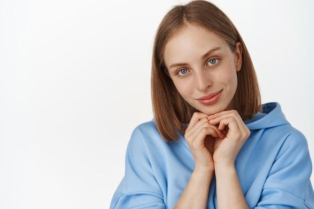 Linda mulher loira feminina com olhos azuis, pele facial limpa e brilhante, mãos dadas perto do rosto, sorrindo e olhando um sonho romântico em frente, parede branca