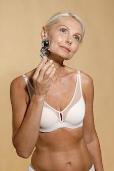 Linda mulher loira madura em roupa íntima com pele brilhante usando rolo facial de metal olhando para longe