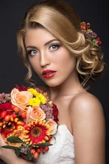 Linda mulher loira na imagem da noiva com flores. rosto de beleza e penteado