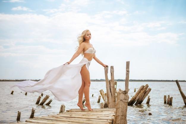 Linda mulher loira na praia em um maiô branco
