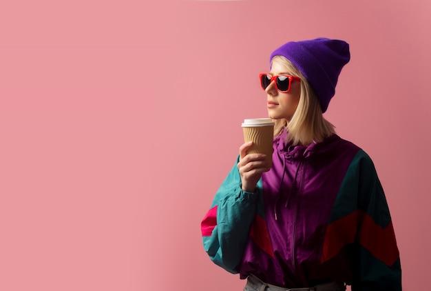 Linda mulher loira na roupa dos anos 90 e café