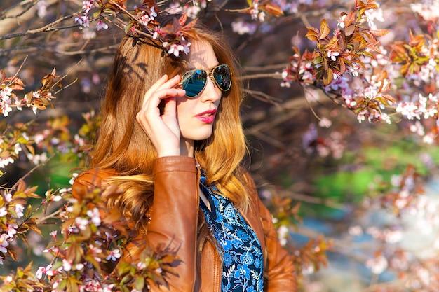 Linda mulher loira no parque em um dia quente de primavera