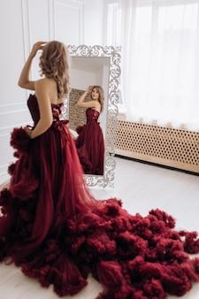 Linda mulher loira no vestido de luxo vermelho burgundi coloca antes de um espelho em um quarto branco