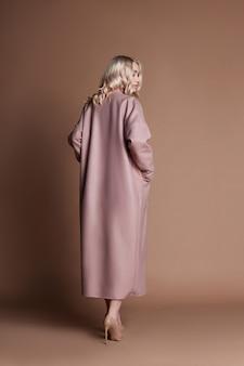 Linda mulher loira posando em um casaco cor de rosa