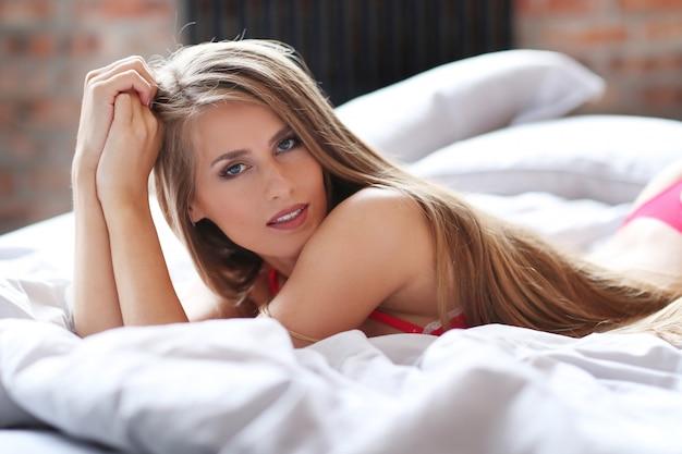 Linda mulher loira posar em roupa interior vermelha na cama