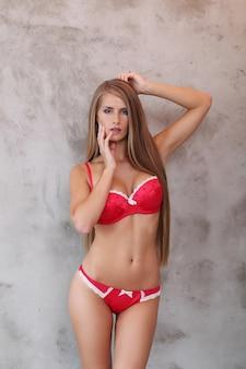 Linda mulher loira posar em roupa interior vermelha