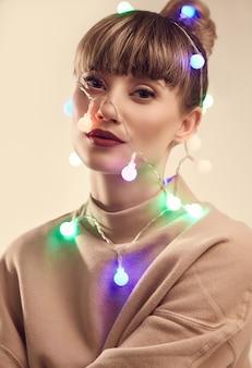 Linda mulher loira positiva com luzes de natal na cabeça
