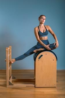 Linda mulher loira positiva está sendo preparada realizando exercícios de pilates, treinamento em equipamentos de barril. conceito de fitness, equipamento especial de fitness. copie o espaço, banner de esporte para publicidade.