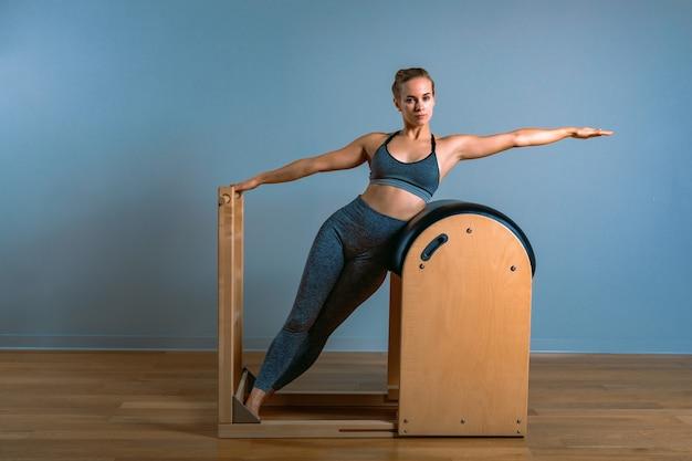 Linda mulher loira positiva sendo preparada fazendo exercícios de pilates no barril