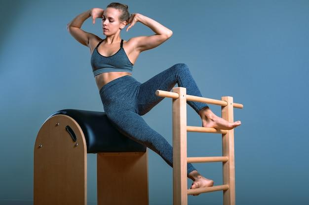 Linda mulher loira positiva sendo preparada realizando exercícios de pilates no barril equi
