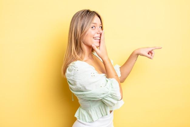 Linda mulher loira se sentindo feliz, chocada e surpresa, cobrindo a boca com a mão e apontando para o espaço lateral da cópia