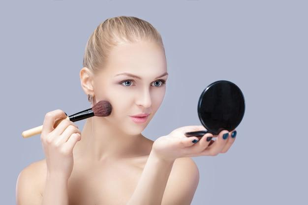 Linda mulher loira segurando o pincel de maquiagem e olhando no espelho em um fundo cinza. fechar-se
