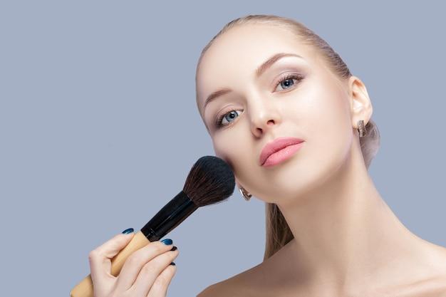 Linda mulher loira segurando o pincel de maquiagem em um fundo cinza. fechar-se