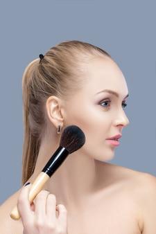 Linda mulher loira segurando o pincel de maquiagem em um fundo cinza. mulher aplicando blush de perto