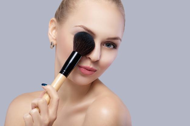 Linda mulher loira segurando o pincel de maquiagem em um fundo cinza.