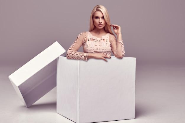 Linda mulher loira sensual vestido rosa posando em uma grande caixa de compras