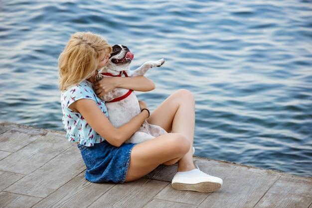 Linda mulher loira sentada, brincando com o bulldog francês perto do mar