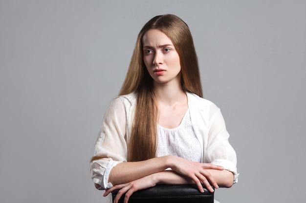 Linda mulher loira sentada no fundo cinza
