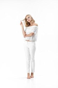 Linda mulher loira séria em uma blusa branca e calça em um fundo branco