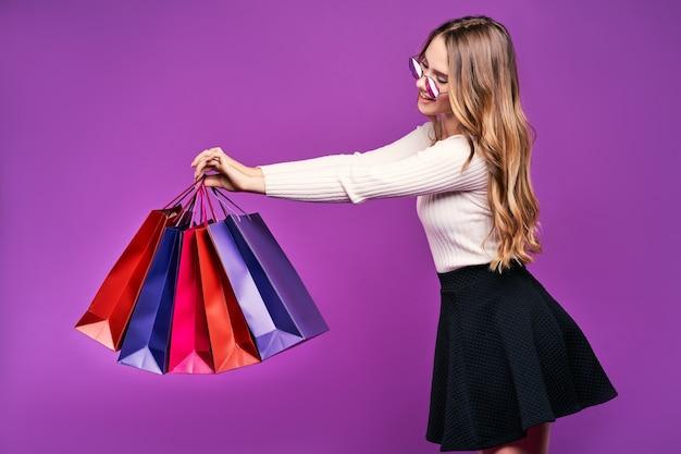 Linda mulher loira sorridente de óculos escuros segurando sacolas de compras em uma parede rosa