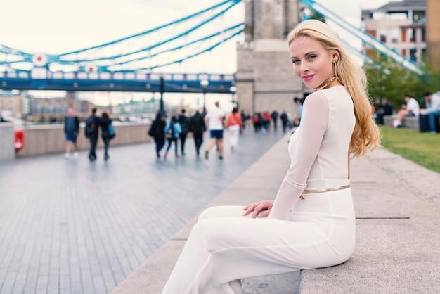Linda mulher loira sorridente em londres com a tower bridge