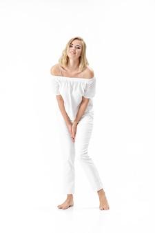 Linda mulher loira sorridente em uma blusa branca e calça em um fundo branco