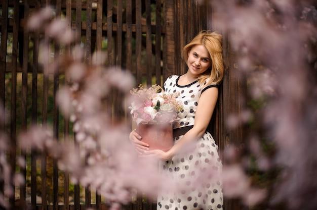 Linda mulher loira sorridente, vestida com um vestido de bolinhas com uma caixa de flores