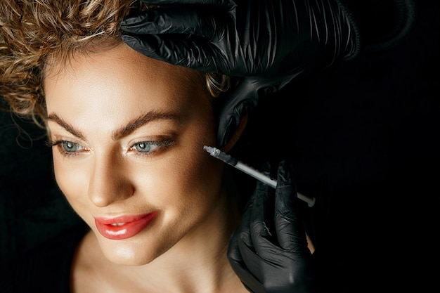 Linda mulher loira tendo injeção de preenchimento em sua bochecha. conceito de cosmetologia. foto de close