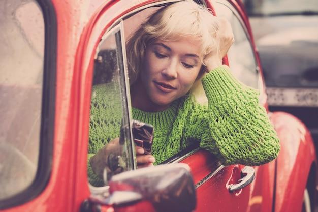 Linda mulher loira usando telefone celular enquanto dirige o carro vermelho no trânsito