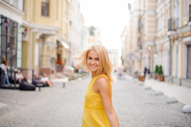 Linda mulher loira, vestida com um vestido amarelo, andando pela cidade