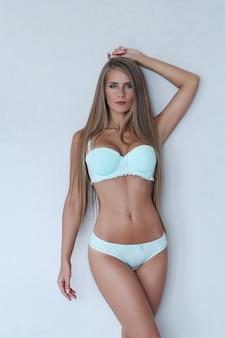Linda mulher loira, vestindo lingerie azul clara