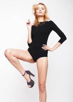 Linda mulher loira vestindo lingerie preta da moda, estúdio filmado sobre fundo branco