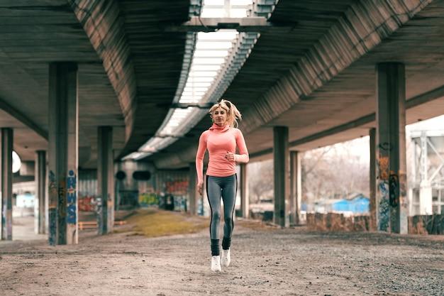 Linda mulher loira, vestindo roupas esportivas e com rabo de cavalo correndo debaixo da ponte.