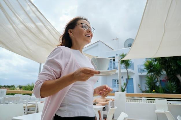 Linda mulher madura, aproveitando as férias no hotel resort, no restaurante, vista da paisagem montanhosa. mulher andando com uma xícara de café. lazer, verão, fim de semana, turismo, viagens pessoas de meia-idade