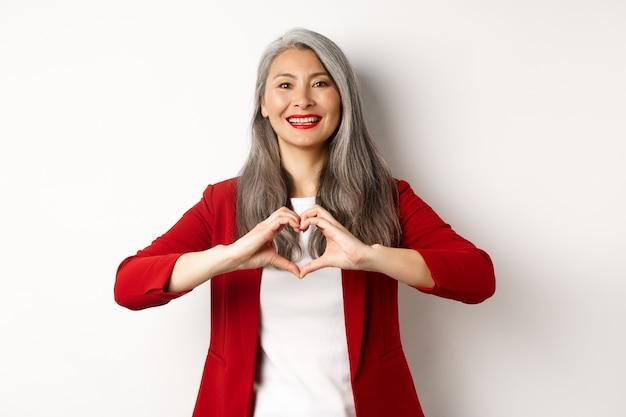 Linda mulher madura asiática em blazer vermelho e maquiagem, mostrando o sinal do coração e sorrindo, eu te amo o gesto, em pé sobre um fundo branco.
