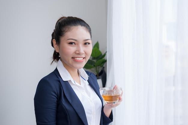 Linda mulher madura bebendo uma xícara de chá em seu escritório. (com espaço de cópia.)