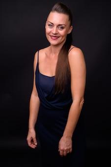 Linda mulher madura com cabelo castanho contra uma parede preta
