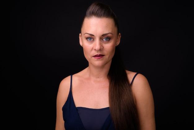 Linda mulher madura com cabelo castanho contra uma parede preta Foto Premium
