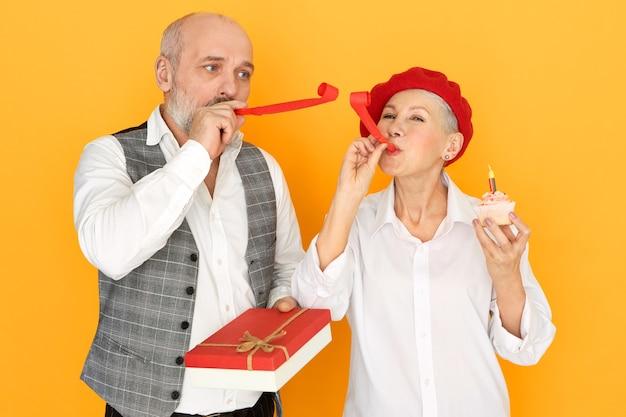Linda mulher madura com cupcake posando ao lado do marido careca sênior segurando um presente na caixa, se divertindo, soprando apito